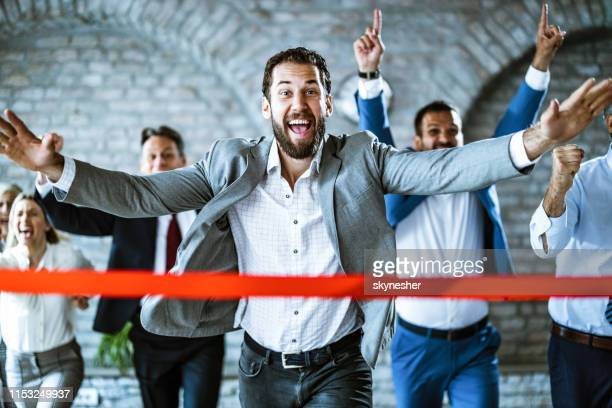 cheerful businessman crossing the finish line on sports race in the office. - finishing line stock pictures, royalty-free photos & images