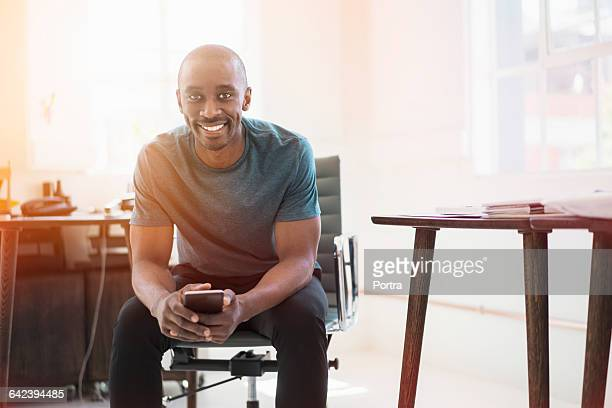 Cheerful businessman holding phone while in office