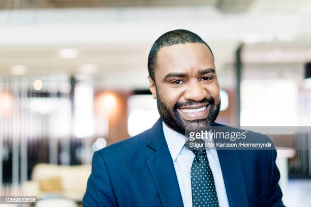 Cheerful businessman in suit standing at office