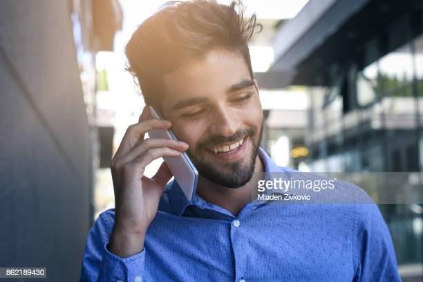 Cheerful businessman on city street using smart phone.