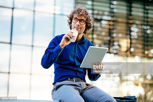 Cheerful businessman reading news on digital tablet