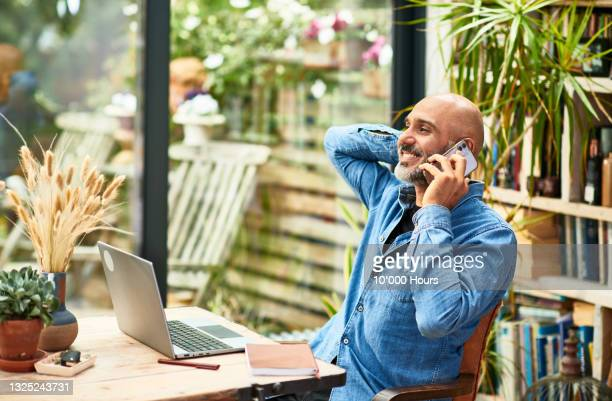 cheerful businessman talking on mobile phone at home - greater london stock pictures, royalty-free photos & images
