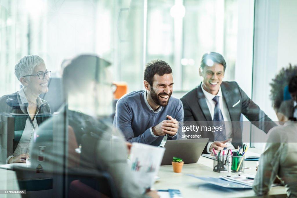 Fröhlicher Geschäftsmann im Gespräch mit seinen Kollegen im Büro. : Stock-Foto