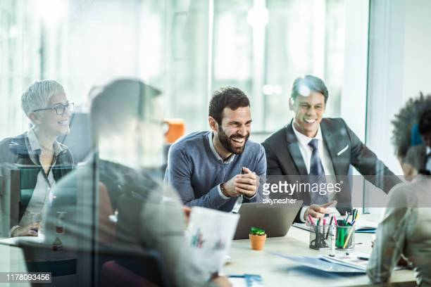 cheerful businessman talking to his colleagues in the office. - riunione commerciale foto e immagini stock