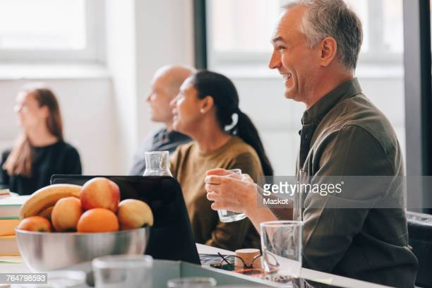 Cheerful businessman team sitting at conference table in board room