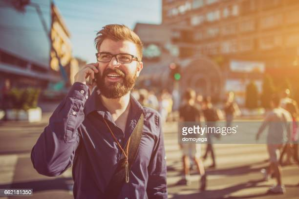 Cheerful businessman using phone in the city street