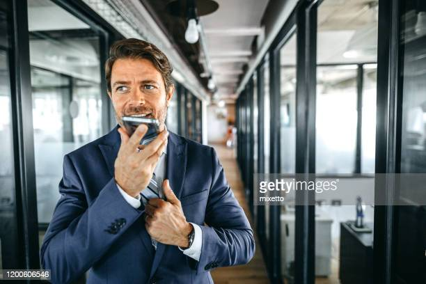 cheerful businessman using smart phone for sending voice message - speech recognition stock pictures, royalty-free photos & images