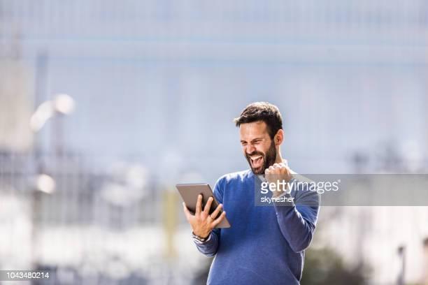 陽気な実業家のタッチパッドを使用して、都市の喜びの悲鳴を上げます。 - ガッツポーズ ストックフォトと画像