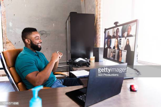 cheerful businessman video chats with colleagues - telecommuting stock pictures, royalty-free photos & images