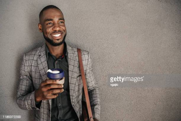 cheerful businessman with cup of hot beverage - shoulder bag stock pictures, royalty-free photos & images