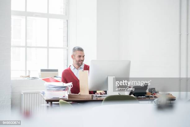 cheerful businessman with grey hair and beard sitting at desk using computer - selective focus stock pictures, royalty-free photos & images