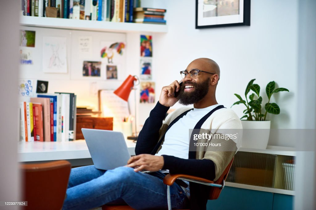 Cheerful businessman working from home on phone : Stock Photo
