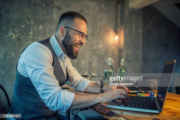 cheerful businessman working on laptop - dusan stankovic stock pictures, royalty-free photos & images