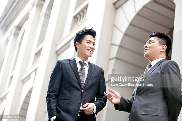 Cheerful businessmen chatting in front a building, Hong Kong