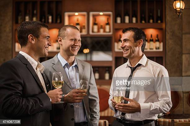Cheerful businessmen communicating in a bar after work.