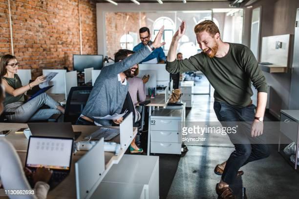glada affärsmän ha roligt samtidigt ge varandra hög-fem på huvudkontoret. - high five bildbanksfoton och bilder
