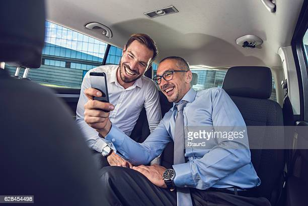Cheerful businessmen having fun while using cell phone in car.