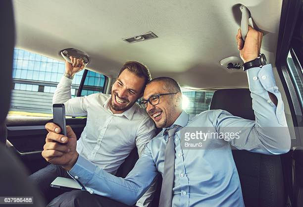 Cheerful businessmen having fun while using mobile phone in car.