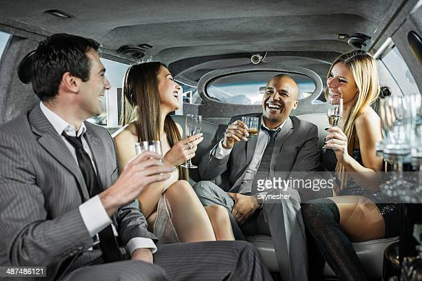 Cheerful businessmen with young women in a limousine.