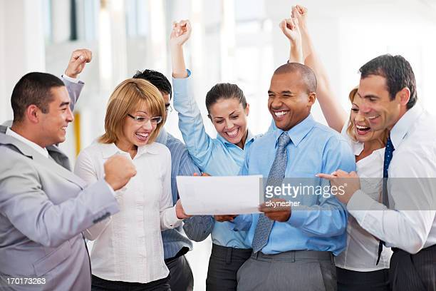 Cheerful businesspeople looking at the report.