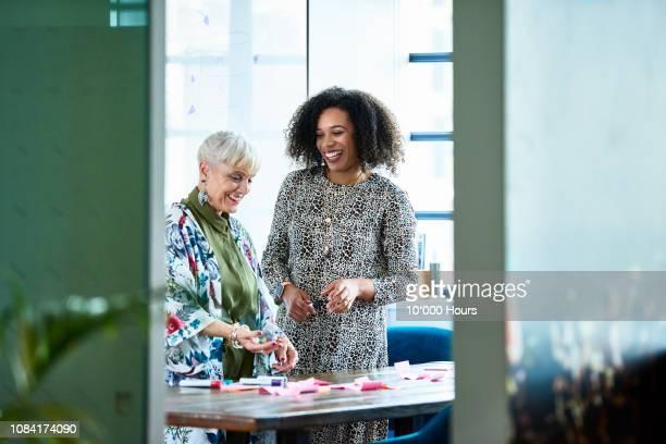 cheerful businesswoman and senior manager planning with sticky notes - thinking outside the box englische redewendung stock-fotos und bilder
