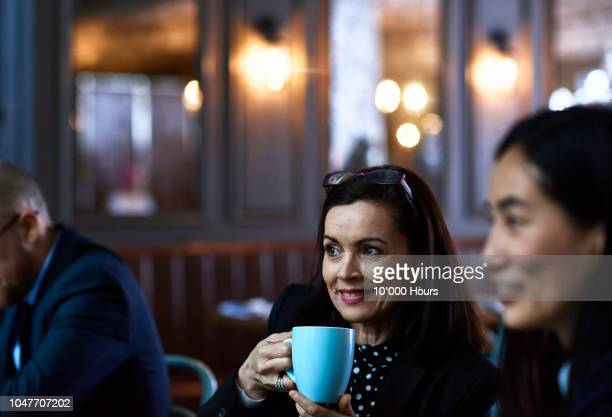 cheerful businesswoman chatting over coffee with colleagues - business casual stock pictures, royalty-free photos & images