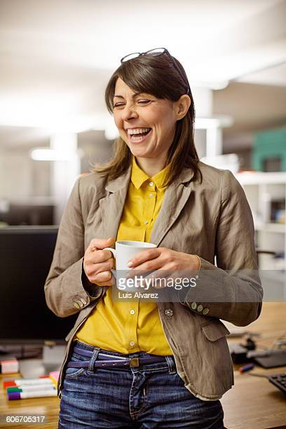 Cheerful businesswoman holding coffee cup