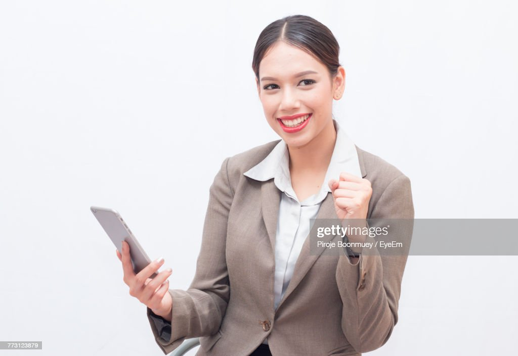 Cheerful Businesswoman Holding Smart Phone Against White Background : Photo