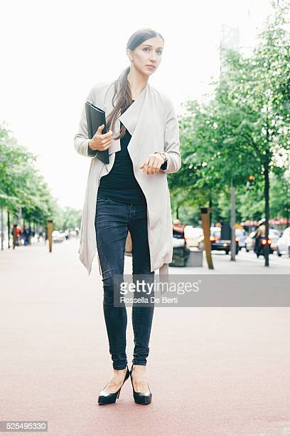 Cheerful Businesswoman In Urban Landscape Looking For A Taxi