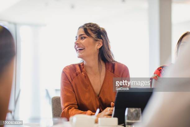 cheerful businesswoman laughing at conference table - office stock pictures, royalty-free photos & images