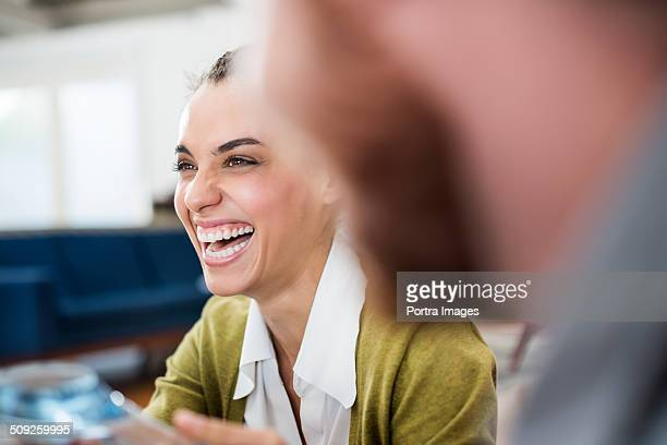 Cheerful businesswoman laughing at creative office