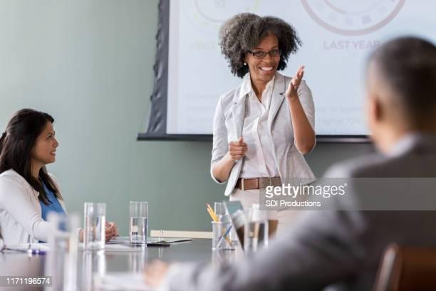 陽気なビジネスウーマンリーディングミーティング - 運営委員会 ストックフォトと画像