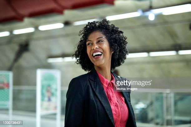 cheerful businesswoman looking away at station - vida urbana - fotografias e filmes do acervo