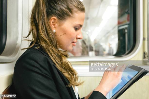 Cheerful Businesswoman On Subway Train Using Digital Tablet