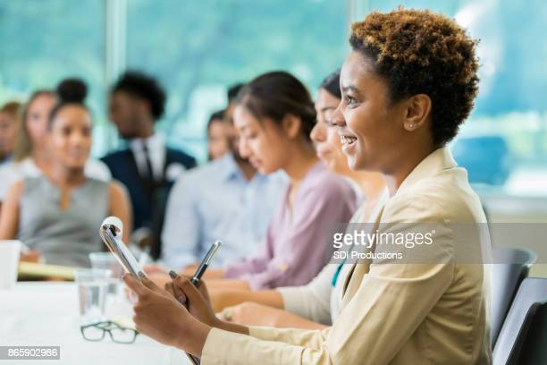 Cheerful businesswoman takes notes during business seminar