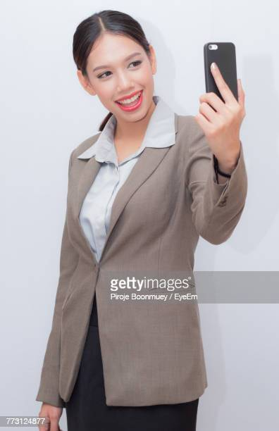 Cheerful Businesswoman Taking Selfie With Smart Phone Against White Background