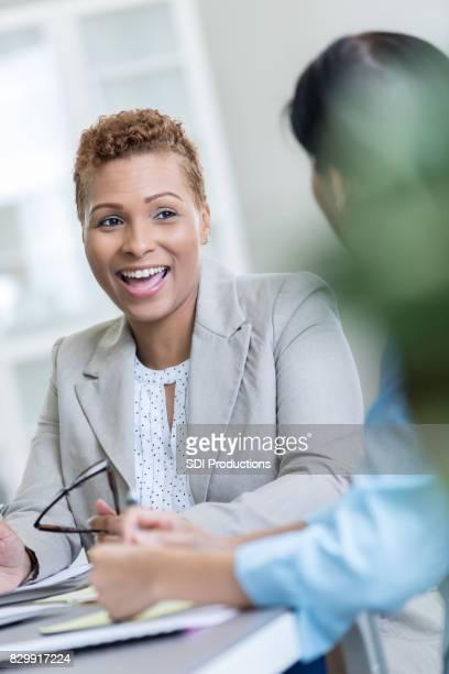 conversaciones de empresaria alegre con el cliente - ayudante fotografías e imágenes de stock