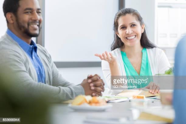 Vrolijke zakenvrouw bijgewerkt collega's tijdens vergadering