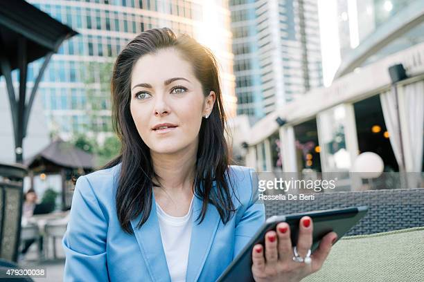 Cheerful Businesswoman Using Digital Tablet During Coffee Break