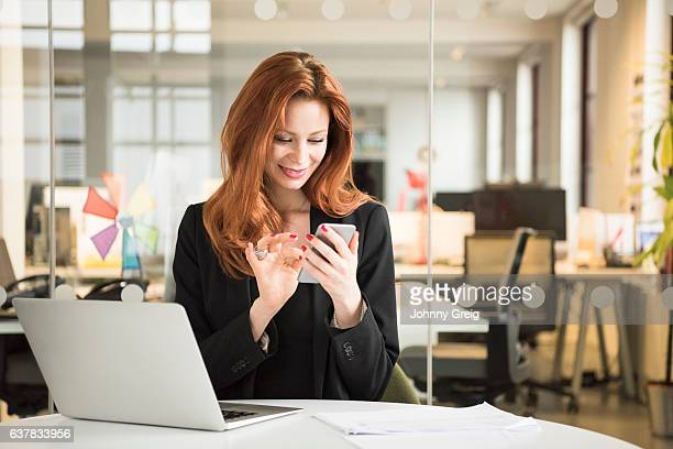 Cheerful businesswoman using smartphone in office, smiling