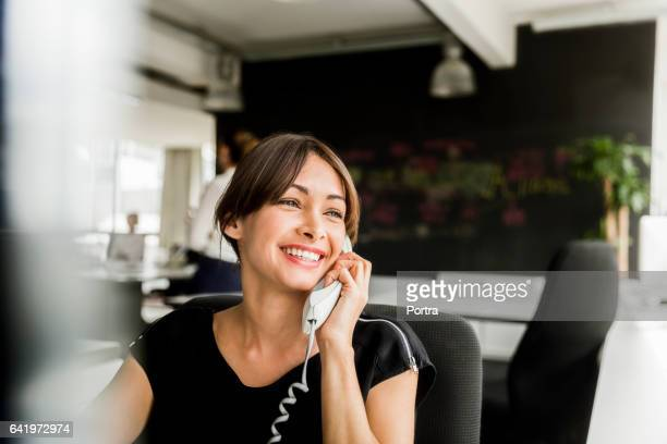 Cheerful businesswoman using telephone in office