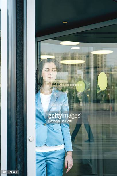 cheerful businesswoman walking through revolving doors - revolve stock photos and pictures