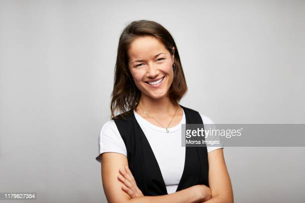 cheerful businesswoman with arms crossed - expertise stock pictures, royalty-free photos & images