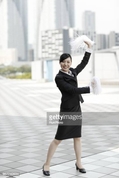 Cheerful businesswoman with pompoms cheering