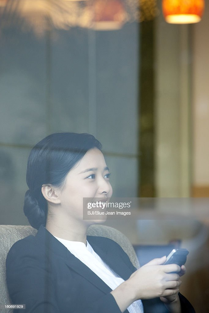 Cheerful businesswoman with smart phone in cafe : Stock Photo