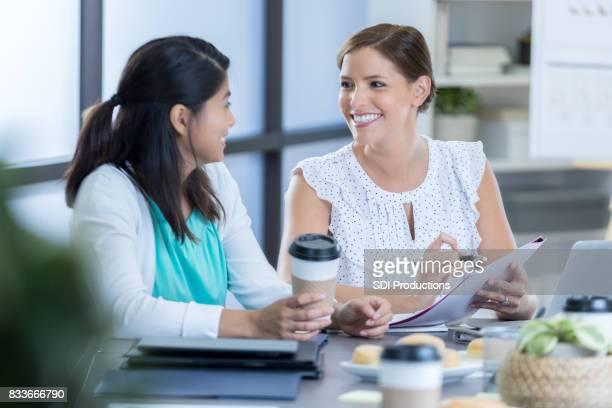 Fröhliche Geschäftsfrauen diskutieren Projekte