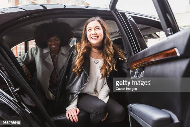 cheerful businesswomen disembarking from car - disembarking stock pictures, royalty-free photos & images