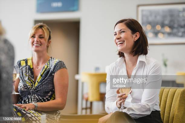 cheerful businesswomen enjoying wine at work social - colleague stock pictures, royalty-free photos & images