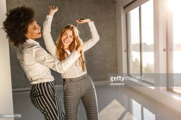 cheerful businesswomen having fun while dancing in the office. - female friendship stock pictures, royalty-free photos & images