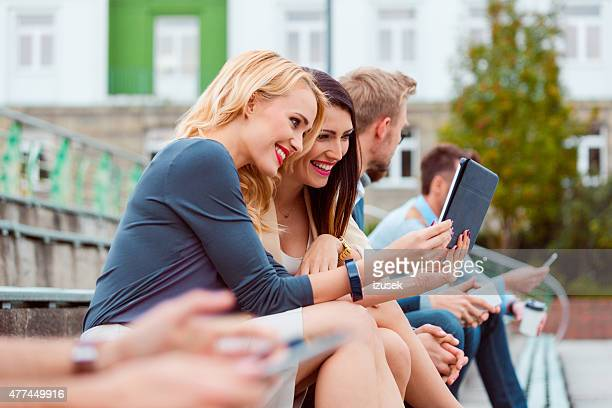 cheerful businesswomen using a digital tablet outdoor - izusek stock photos and pictures